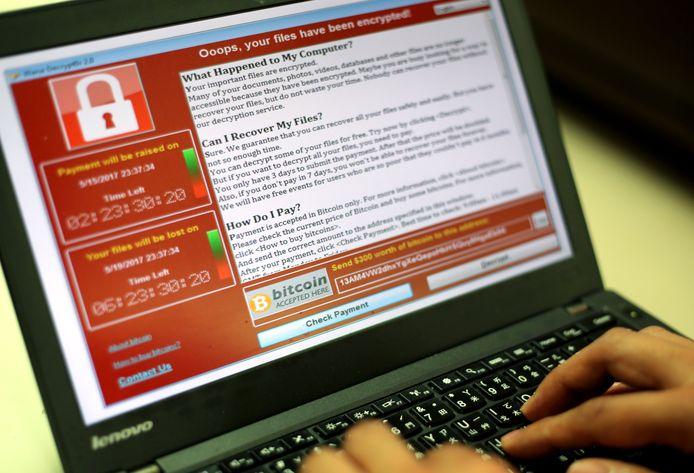Een programmeur toont een laptop waarvan de bestanden versleuteld werden door de ransomsofware 'WannaCry'.