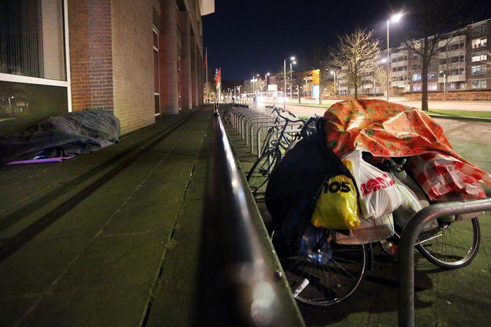 Een dakloze man slaapt naast het stadskantoor van de gemeente Breda.