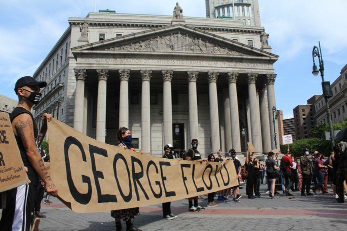 Demonstranten met een spandoek met daarop de naam van George Floyd voor de rechtbank van New York.