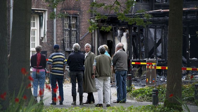 Burgemeester Henri de Wijkerslooth (M), wethouders en medewerkers maken een ronde langs de resten van het gemeentehuis. Beeld anp