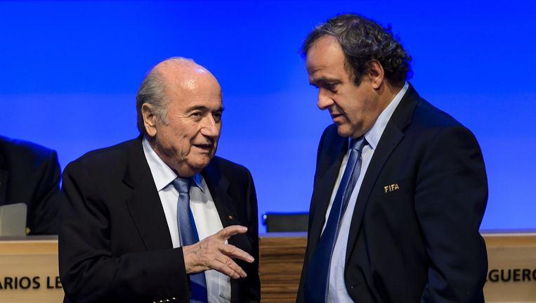 Joseph Blatter praat met Michel Platini. Beeld anp