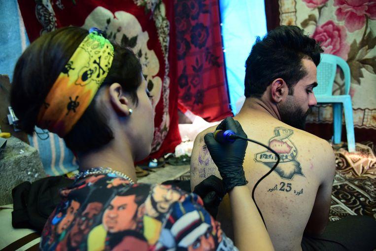 Een vrouw zet een tatoeage met de tekst '25 oktober-revolutie' op de rug van een man. Op die datum was er een harde confrontatie tussen demonstranten en de regering. Beeld EPA