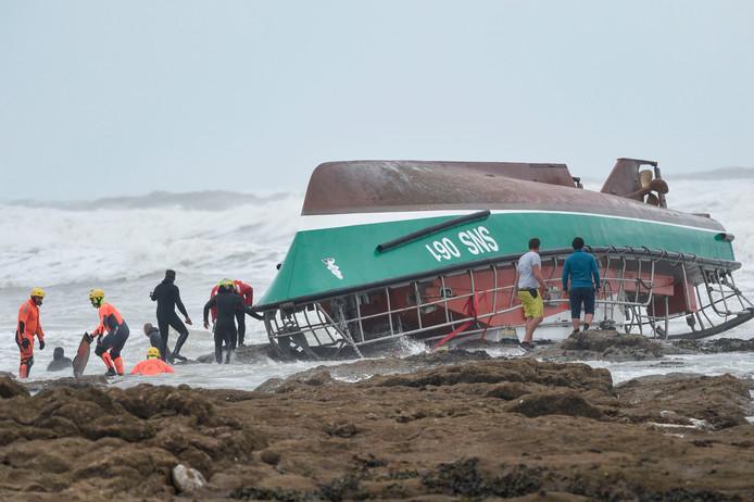 Brandweerlieden, reddingswerkers en medewerkers van de Franse zeevaartautoriteit stellen voorwerpen veilig van de gekapseisde en daarna op de rotsen geslingerde reddingsboot SNS 061 Jack Morisseau