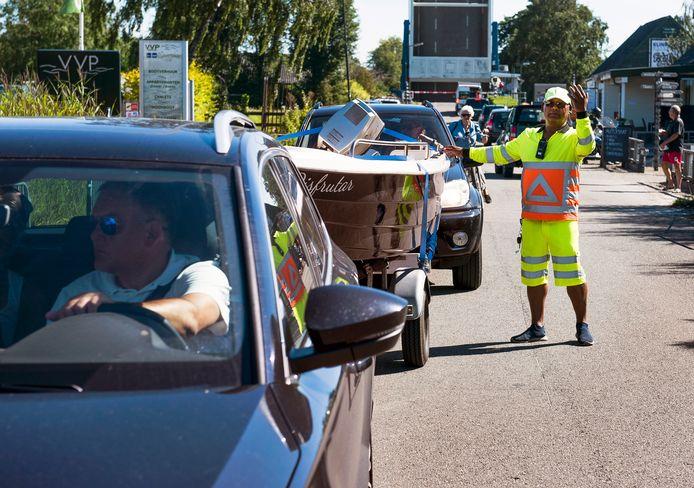 Verkeersregelaar Hendrik leidt het verkeer op de Baambrugse Zuwe in goede banen. Vanwege de tropische hitte is het extra druk bij de Vinkeveense plassen.