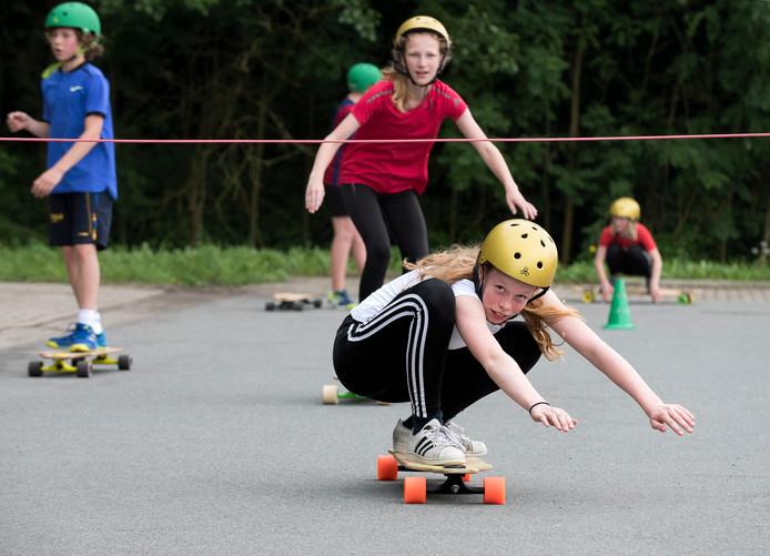 Bij Kampong kunnen middelbare scholieren kennismaken met diverse sporten: Op een longboard onder een lijn door.