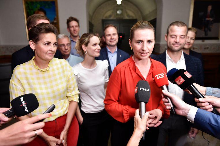 Mette Frederiksen (in het rood) spreekt de pers toe.