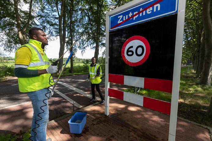 Zutphen krijgt weer schone verkeers- en straatnaamborden dankzij Frank en Samuel van het asielzoekerscentrum.