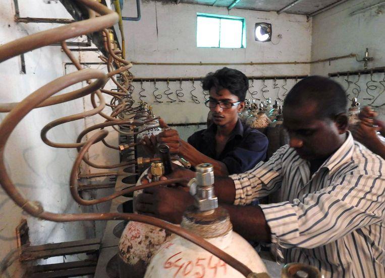 Na de sterfgevallen van vorige maand controleren medewerkers van het Baba Raghav Das-ziekenhuis de cilinders die het staatshospitaal van zuurstof moeten voorzien. Beeld AFP