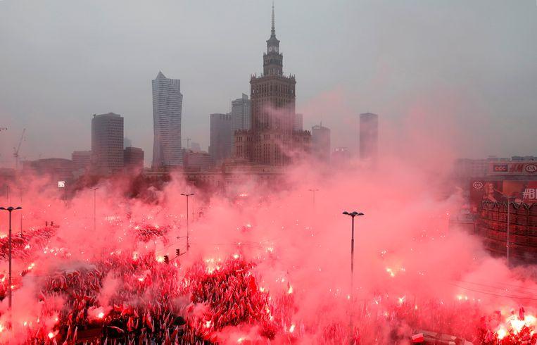 Warschau zondag, volgestroomd met zeker 200 duizend Polen, met wit-rode vlaggetjes, die 'God, eer, vaderland' scanderen. Beeld REUTERS