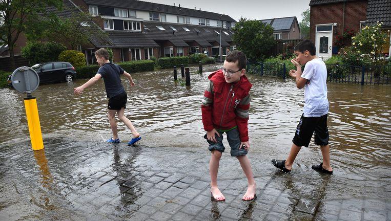 Kinderen spelen in een ondergelopen straat in Boxmeer, waar begin juni binnen enkele uren 100 mm regen viel. Beeld Marcel van den Bergh / de Volkskrant