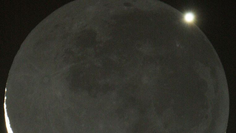 Venus zichtbaar boven de maan, op 17 mei 2010. Beeld EPA