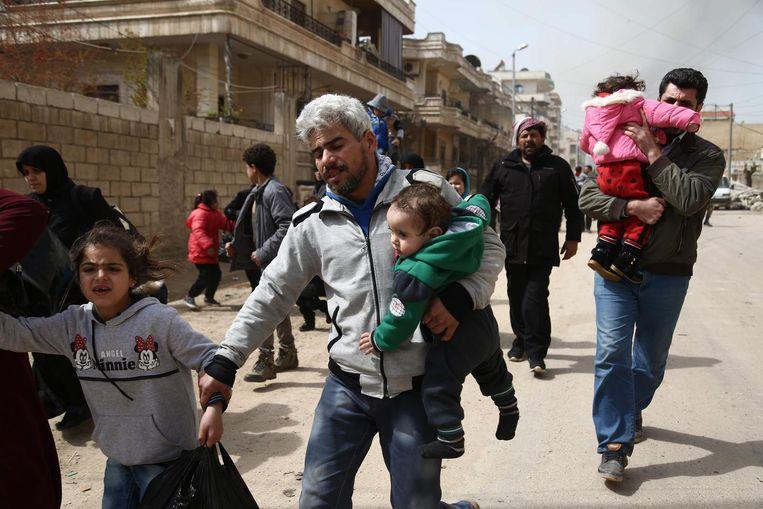 Inwoners van Afrin rennen voor hun leven, weg van de explosies in de stad. Beeld afp