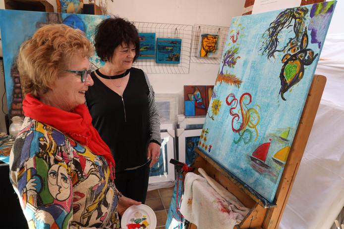 Kunstenares Sia Braakman (rechts) bewondert samen met Riet de Sutter het gemeenschappelijke schilderij