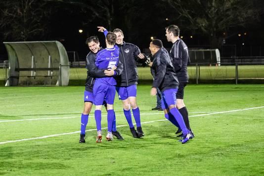 SSV'65-speler Rowan Amperse (nummer vijf) wordt besprongen door zijn ploeggenoten nadat hij de beslissende strafschop heeft binnengeschoten.