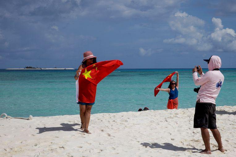 Chinese toeristen poseren op Qanfu, een van Paracel-eilanden  Beeld AP