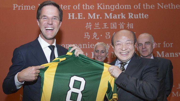 (Archieffoto 2015) Premier Mark Rutte kijkt naar een shirt van ADO Den Haag met zijn fout gespelde naam erop dat hij kreeg van de nieuwe Chinese eigenaar van ADO, Hui Wang (R) tijdens de eerste dag van een 4-daags handelsmissie aan China. Beeld anp
