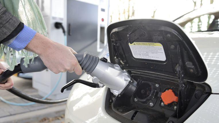 Een automobilist laadt zijn elektrische auto op. Beeld anp