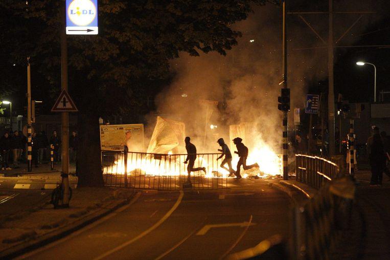 Relschoppers rennen langs een barricade van vuur in de Schilderswijk. Beeld epa