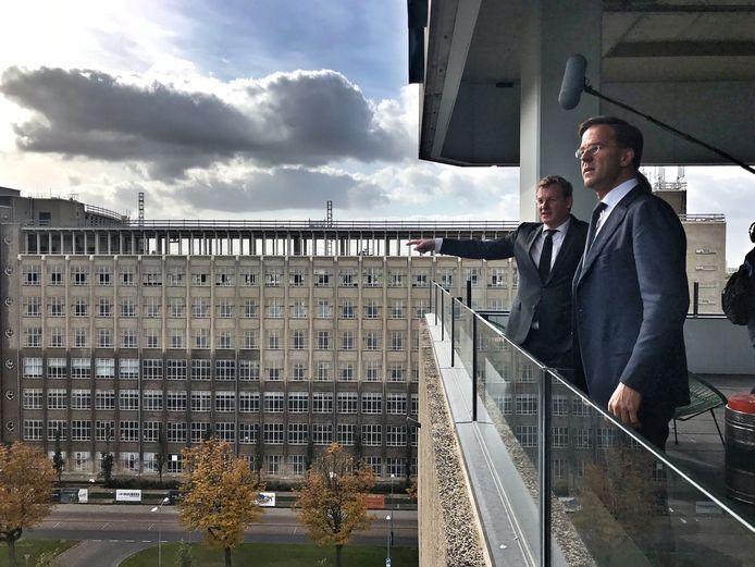 Brainport-directeur Paul van Nunen (links) en Mark Rutte die  op werkbezoek is op Strijp-S in Eindhoven. Op de achtergrond de voormalige Philips Bedrijfsschool, het gebouw wordt verbouwd tot appartementencomplex.