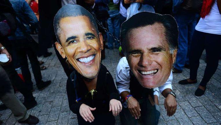 Twee Occupy-demonstranten dragen maskers van de presidentskandidaten. Beeld ANP