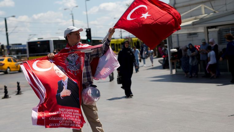 Een straatverkoper toont zijn assortiment aan vlaggen die uiting geven aan support voor president Erdogan. Beeld ap