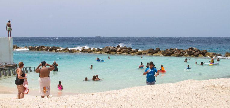 Badgasten op het strand van Willemstad, half mei. De stranden waren enkele weken nagenoeg verlaten, maar het openbare leven op Curaçao komt weer op gang nadat de lockdown werd versoepeld. Beeld ANP