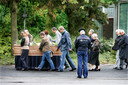 Familieleden begeleiden, onder toezicht van de politie, de kist van Karst Tates naar zijn laatste rustplek.