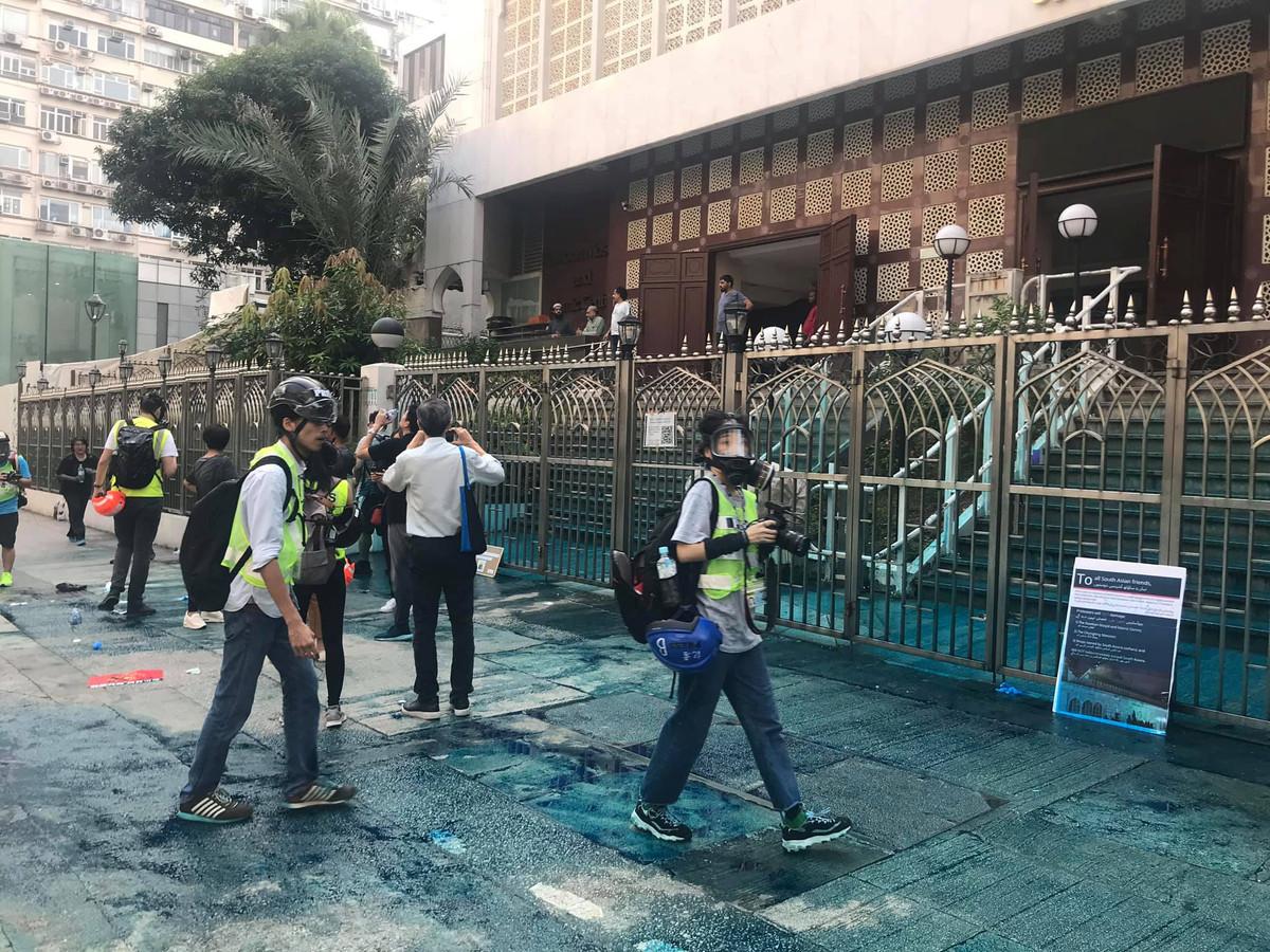 Verslaggevers voor de met blauwe verf bevuilde entree van de Kowloon-moskee in Hongkong.