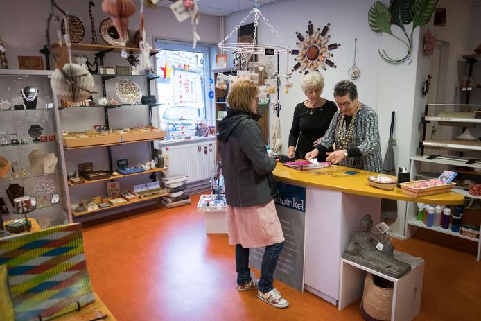 Tonny Dingemans (achter de toonbank links) en Jopie den Teuling helpen een klant in de Wereldwinkel in Huissen.