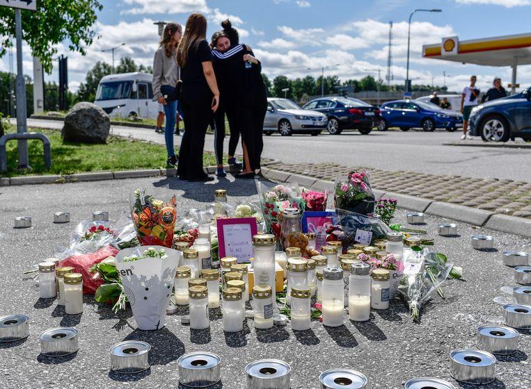 Mensen plaatsen kaarsjes en leggen bloemen bij de plaats delict: een tankstation in Botkyrka ten zuiden van Stockholm. Beeld Hollandse Hoogte / EPA
