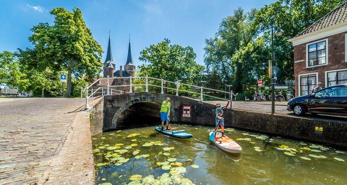Arie en Wout van der Stap peddelen over het water langs de Oostpoort.