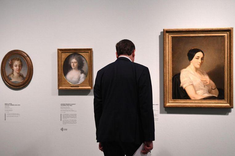 Een schilderij van Thomas Couture (rechts) wordt bekeken door een bezoeker. Beeld epa
