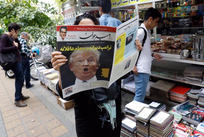 Een Iraanse vrouw  leest een krant met Trump op de voorpagina. De Amerikaanse president is groot tegenstander van de kerndeal  het land.