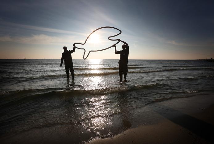 Gedeputeerde Johannes Kramer van Provincie Fryslan houdt samen met de oud-directeur Waddenvereniging Arjan Berkhuysen een metalen vis omhoog tijdens de startsein voor het creëren van een vismigratierivier in de Afsluitdijk eind 2014.