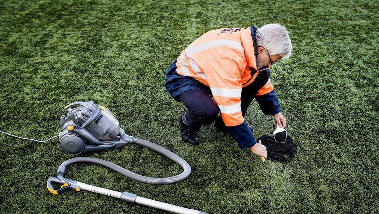 Een medewerker van Vereniging Band en Milieu verzamelt de rubberkorrels van de kunstgrasmat van de voetbalvereniging Roda 23. Beeld null