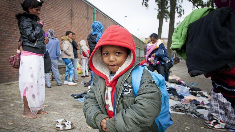 Vluchtelingen zoeken in Rotterdam kleding uit die buurtbewoners naar een opvangcentrum hebben gebracht. Beeld anp