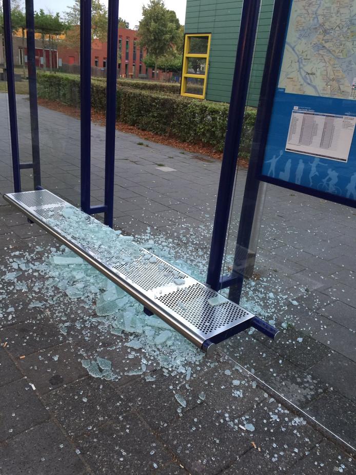 Door de vernielingen ligt veel glas op het bankje en op de grond bij de bushalte aan het Bachplein.