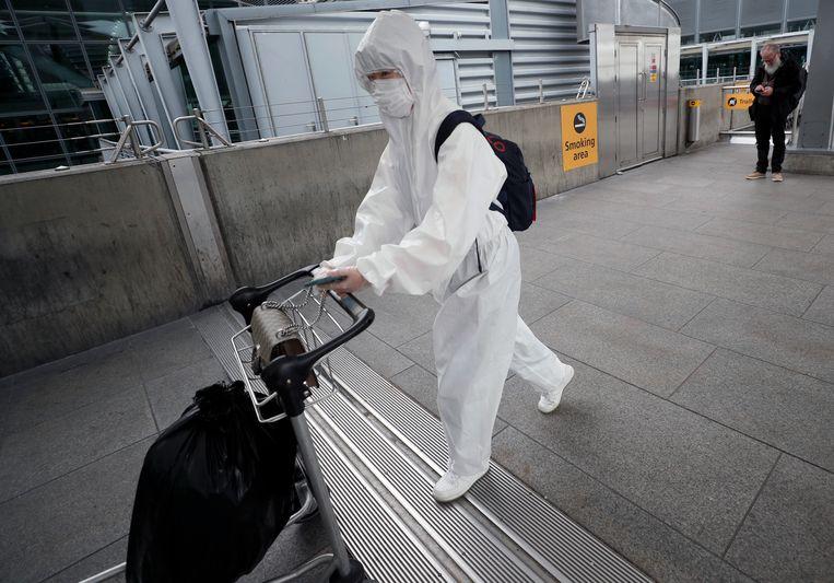Een volledig in beschermde kleding ingepakte reiziger op  Heathrow airport in Londen. Beeld AP