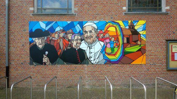 In het werk zijn pastoor Adriaan Eykens, de Antwerpse bisschop Johan Bonny en paus Franciscus te zien.