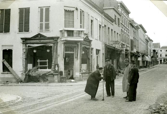 Foto van Nico Kramer van de hoek van de Spijkerlaan en de Spijkerstraat, in het Arnhem van kort na de bevrijding, maar voor de terugkeer van de bevolking. Gemeenteambtenaren controleren de waterleiding. Op de achtergrond de voormalige slagerij Brinkhoff, thans restaurant De Blauwe Hoek.