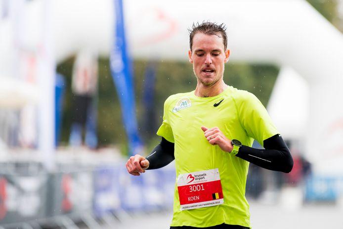 Een doorregende Koen Naert overschrijdt als tweede de finishlijn van de halve marathon