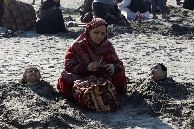 Een vrouw zit naast twee kinderen die tot het hoofd zijn ingegraven in het zand. In Pakistan heerst het bijgeloof dat dit tijdens een zonsverduistering voor genezing kan zorgen.