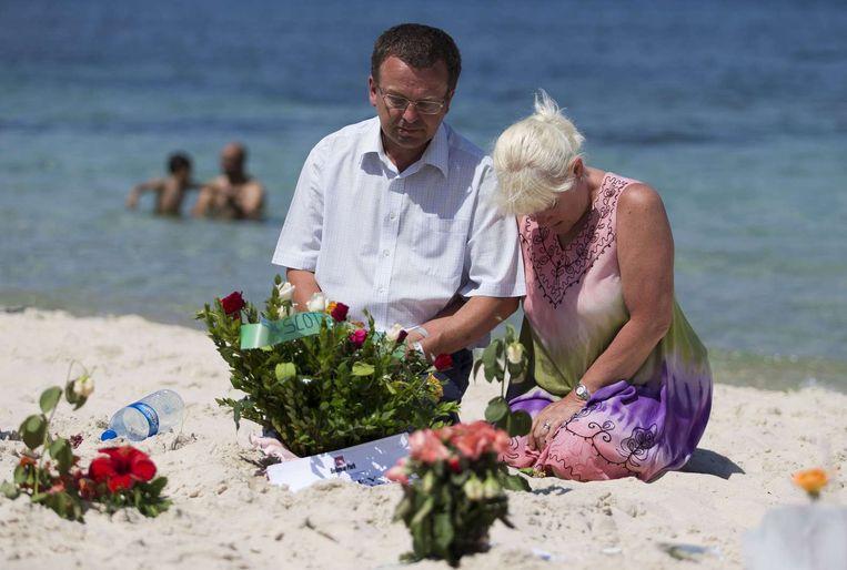 Een man en een vrouw rouwen op de plek van de schietpartij. Beeld afp