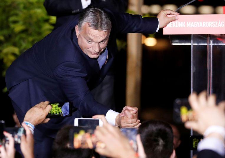 De Hongaarse premier Viktor Orbán schudt aanhangers de hand. Beeld Reuters