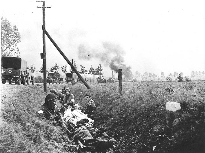Gewonde Britse soldaten liggen in een greppel. Mannen van het Rode Kruis helpen hen. De operatie Market Garden eindigde in een catastrofe.