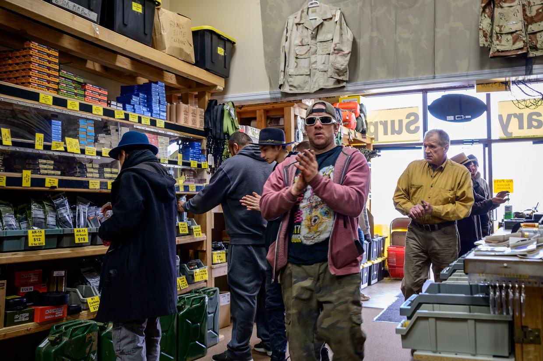 Bij Priority One, een wapenwinkel in Hamburg, Pennsylvania, liggen de verkopen drie keer zo hoog als op een Black Friday. Klanten wrijven hun handen in met ontsmettingsmiddel. Beeld Cynthia van Elk