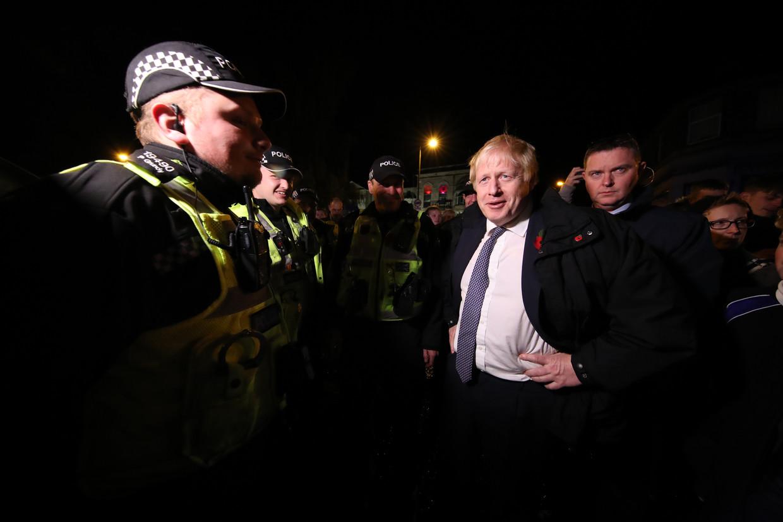 Premier Boris Johnson tijdens een bezoek aan Matlock dat geteisterd werd door hevige regen.  Beeld Getty Images