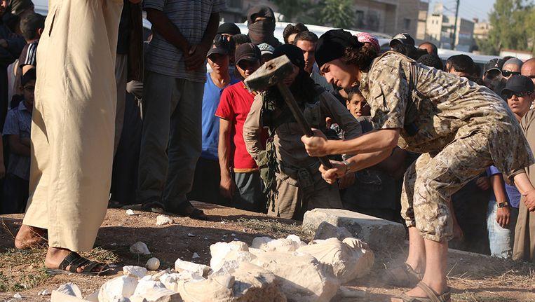 Een IS-militant vernielt met een voorhamer archeologische schatten in Palmyra. (Archieffoto)