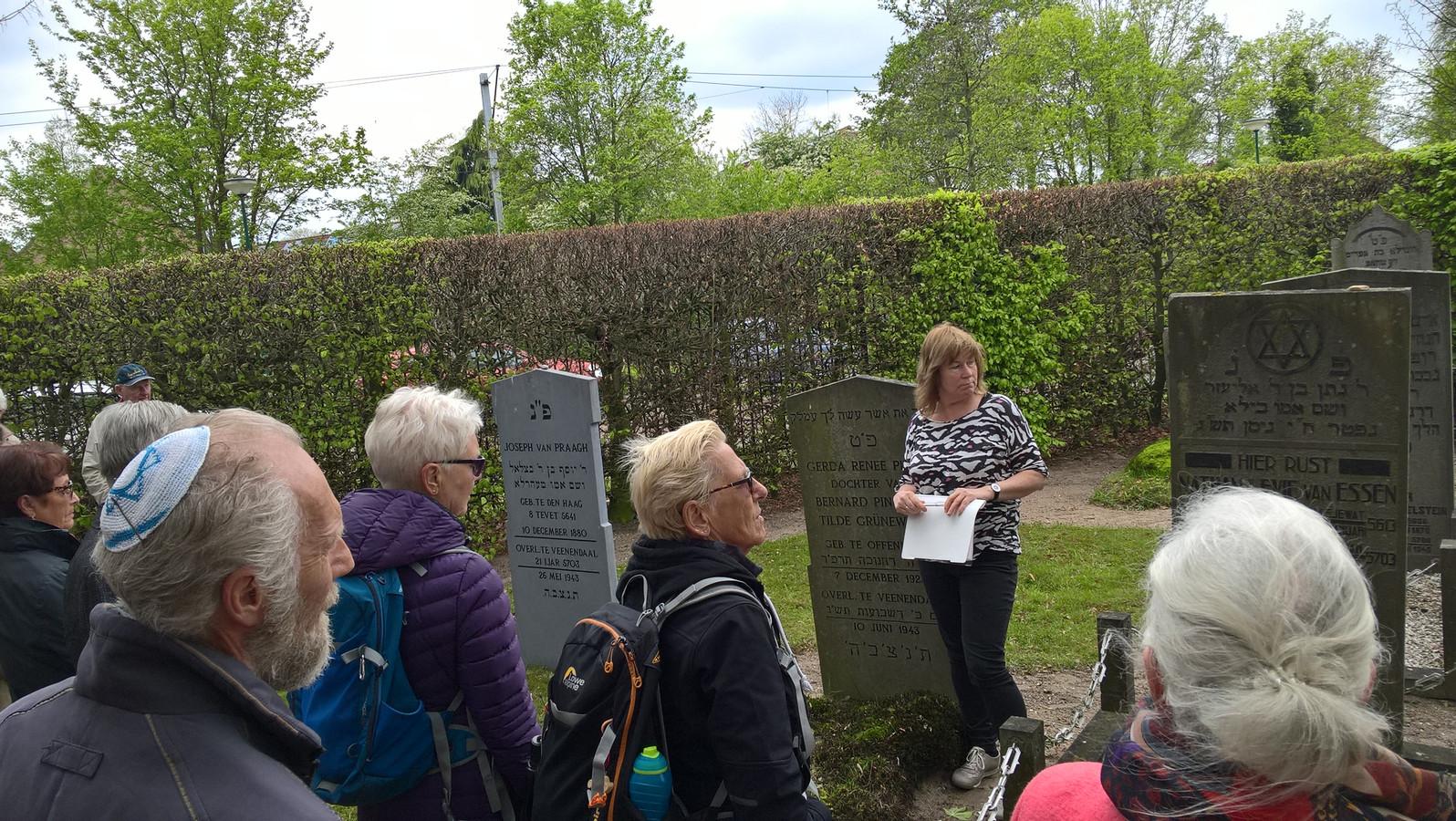Wilke Middelhoven vertelt naast een grafsteen over de Joodse geschiedenis van Veenendaal.