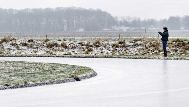 Een man fotografeert de ijsbaan in Noordlaren waar dinsdag de eerste marathon op natuurijs van deze winter wordt verreden. Beeld anp